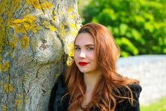 Muchacha sonriente linda que mira la lente en naturaleza contra un árbol fotos de archivo
