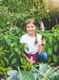 Muchacha sonriente linda que presenta con la paleta en el jardín floreciente Fotos de archivo