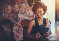 Muchacha sonriente negra con el cojín digital en sala de reunión Imagenes de archivo