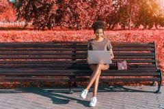 Muchacha sonriente negra con el netbook, colores rojos en vez del verdor imagen de archivo libre de regalías