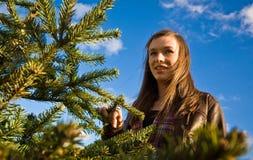 Muchacha sonriente por el árbol de navidad Foto de archivo