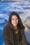 Muchacha sonriente por la fuente Imagen de archivo libre de regalías