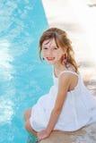 Muchacha sonriente por una piscina al aire libre imagen de archivo