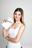 Muchacha sonriente positiva joven del estudiante con el cuaderno y pluma que la planea horario diario que lleva la camiseta blanc Imagen de archivo libre de regalías