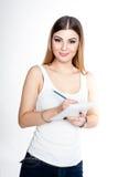 Muchacha sonriente positiva joven del estudiante con el cuaderno y pluma que la planea horario diario que lleva la camiseta blanc Fotografía de archivo libre de regalías