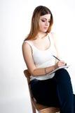Muchacha sonriente positiva joven del estudiante con el cuaderno y pluma que la planea horario diario que lleva la camiseta blanc Fotos de archivo libres de regalías