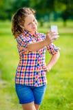 Muchacha sonriente preciosa que plantea y que toma el selfie con smartphone Foto de archivo libre de regalías