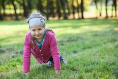 Muchacha sonriente preescolar que hace exercices de los pectorales en hierba verde en parque Imagen de archivo