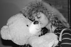 Muchacha sonriente que abraza el pelouche formado oso Fotografía de archivo