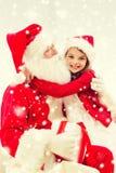 Muchacha sonriente que abraza a Papá Noel con el regalo en casa Foto de archivo libre de regalías