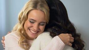 Muchacha sonriente que abraza a su amigo moreno, celebrando buenas noticias, amistad metrajes