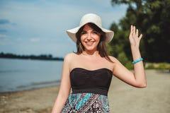 Muchacha sonriente que agita en la playa fotos de archivo