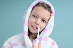 Muchacha sonriente que aprende aplicar los dientes con brocha Imagen de archivo libre de regalías