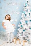 Muchacha sonriente que baila casi el árbol de navidad con las decoraciones y los presentes de la Navidad Imagen de archivo libre de regalías