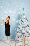 Muchacha sonriente que baila casi el árbol de navidad con las decoraciones y los presentes de la Navidad Fotografía de archivo