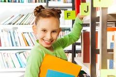 Muchacha sonriente que busca los libros en biblioteca Foto de archivo