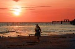 Muchacha sonriente que camina en la playa hermosa en la puesta del sol Fotos de archivo