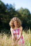 Muchacha sonriente que camina a través de hierba alta Imagen de archivo libre de regalías