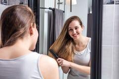 Muchacha sonriente que cepilla su pelo largo delante del espejo Fotografía de archivo
