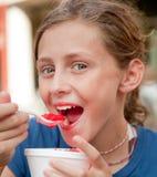 Muchacha sonriente que come un cono de la nieve Fotografía de archivo