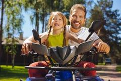 Muchacha sonriente que conduce ATV con su papá Foto de archivo libre de regalías