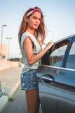 Muchacha sonriente que consigue en el coche fotografía de archivo libre de regalías