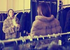 Muchacha sonriente que decide sobre la opción del abrigo de pieles fotografía de archivo libre de regalías