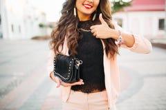 Muchacha sonriente que demuestra el bolso con el pulgar para arriba Foto de archivo libre de regalías