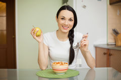 Muchacha sonriente que desayuna con muesli y la manzana Fotos de archivo libres de regalías