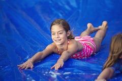 Muchacha sonriente que desliza abajo un resbalón y una diapositiva al aire libre Fotos de archivo libres de regalías