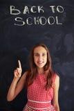 Muchacha sonriente que destaca en de nuevo a la inscripción de la tiza de la escuela encendido Imagen de archivo