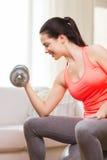 Muchacha sonriente que ejercita con pesas de gimnasia Imagen de archivo libre de regalías