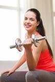 Muchacha sonriente que ejercita con pesas de gimnasia Imagen de archivo