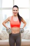Muchacha sonriente que ejercita con pesas de gimnasia Fotografía de archivo libre de regalías