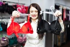 Muchacha sonriente que elige la ropa interior Fotos de archivo