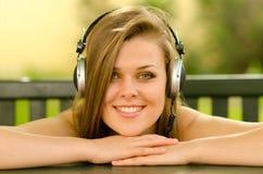 Muchacha sonriente que escucha la música Imágenes de archivo libres de regalías
