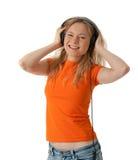 Muchacha sonriente que escucha la música en auriculares Imagenes de archivo