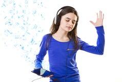 Muchacha sonriente que escucha la música en la tableta digital  Foto de archivo libre de regalías