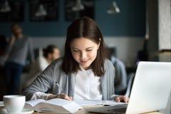 Muchacha sonriente que estudia en notas de la escritura del café en libro de ejercicio Imagenes de archivo