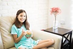 Muchacha sonriente que goza del desayuno del cereal en casa fotografía de archivo libre de regalías