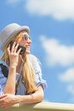 Muchacha sonriente que habla el teléfono móvil contra el cielo Foto de archivo libre de regalías