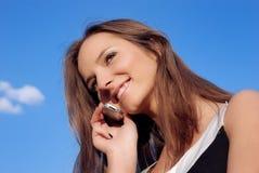 Muchacha sonriente que habla en el teléfono al aire libre Fotos de archivo