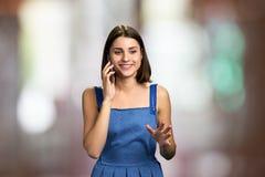 Muchacha sonriente que habla en el teléfono celular fotos de archivo