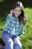 Muchacha sonriente que habla en el teléfono celular Imagen de archivo libre de regalías