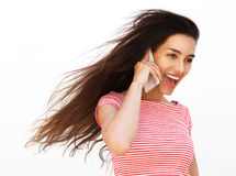 Muchacha sonriente que habla en el teléfono móvil con el pelo que sopla en el viento Fotografía de archivo libre de regalías