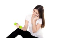 Muchacha sonriente que habla en el teléfono y pesas de gimnasia de elevación Foto de archivo
