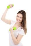 Muchacha sonriente que habla en el teléfono y pesas de gimnasia de elevación Fotografía de archivo