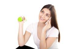 Muchacha sonriente que habla en el teléfono y pesas de gimnasia de elevación del color verde Fotos de archivo