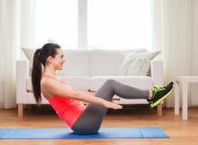 Muchacha sonriente que hace ejercicio en piso en casa Imagen de archivo libre de regalías