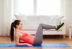 Muchacha sonriente que hace ejercicio en piso en casa Imagen de archivo